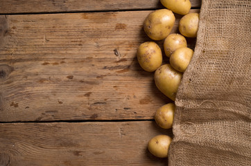 potatoes in burlap sack on wooden background