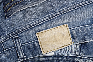 Blank real leather jeans label sewed on old worn blue jeans.