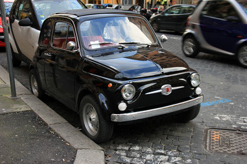 funny black small old little italian car with round headlights a