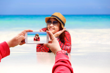 Smartphone photographing Asia woman in Tropical beach, Similan Island, Koh Ta Chai, Andaman Sea, Thailand