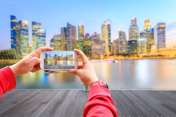 Smartphone photographing landscape of the Singapore financial district and business building