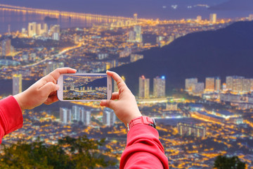 Smartphone photographing Top view of Georgetown, capital of Penang Island, Malaysia from top of Penang hill.
