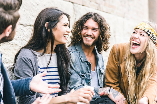 Group of four friends laughing out loud outdoor, sharing good mood