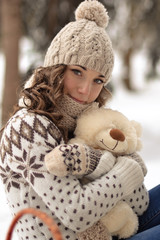 Beautiful,happy,smiling,little,wearing sweater,hut,mittens,patterns,little girl with a small,cute,white,beige,soft,fluffy,little teddy bear in snow,cold,winter forest.December.January.February.Care
