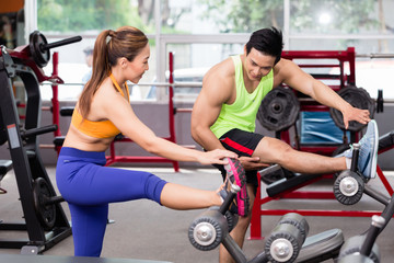 woman and instructor standing in gym stretching legs