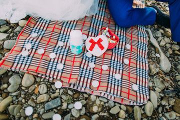 Romantic picnic on a river shore: tartan cloth, candles and box with candies