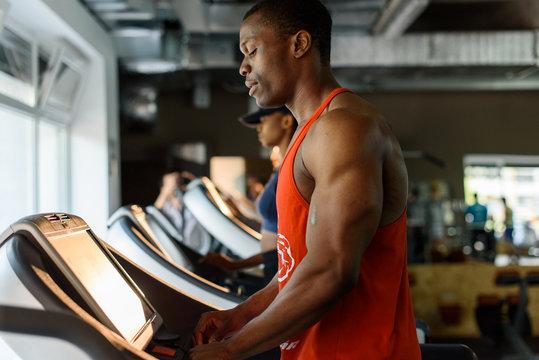Black african american bodybuilder training on the treadmill in gym