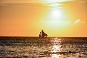 Sunset in Boracay, Philippines with a person that swim