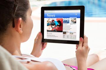 Woman Reading News On Digital Tablet