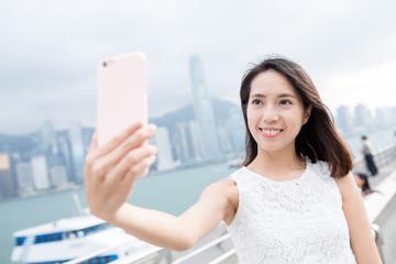 Woman take self picture in landmark of Hong Kong