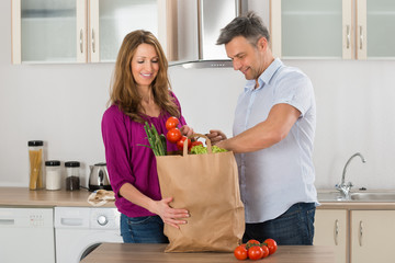 Couple Removing Vegetables From Grocery Bag