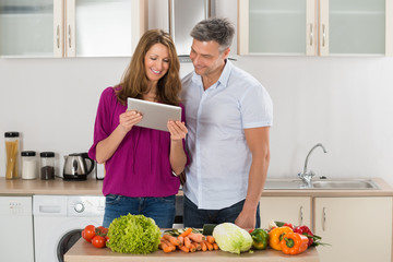Couple Looking At Recipe On Digital Tablet