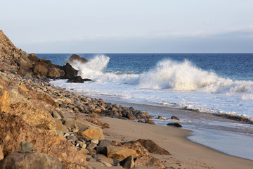 Beach landscape in Malibu. The ocean and waves during strong winds in United States, California. Waves breaking on the rocks.
