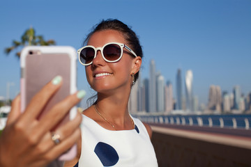 Tourist woman taking mobile phone selfie picture at Dubai.
