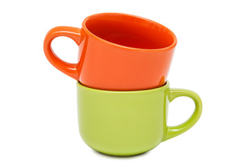 Two colorful ceramic cups stand on each other on a white backgro