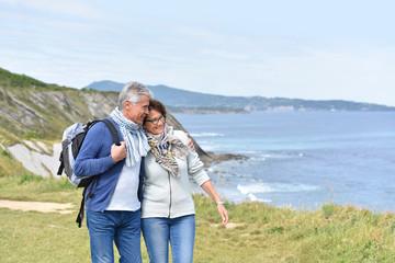 Senior couple walking by sea cliff