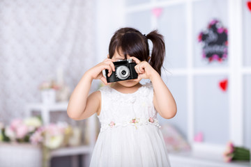 cute little girl holding an old camera. child taking pictures on an old camera