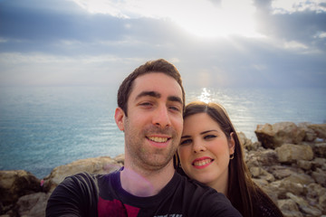 Happy couple taking selfie with smartphone or camera over sunset