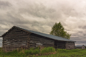 Two Barn Houses Under The Storm Clouds