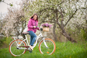 Active female biker wearing purple jacket and jeans starting to ride a vintage white bicycle and lilac flowers basket, against the background of blooming trees in spring garden