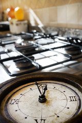 time for lunch with an old clock on a stove-top