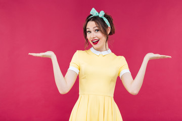 Smiling pinup girl in yellow dress holding copyspace on palms