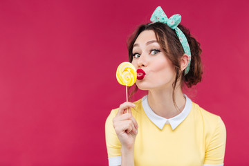 Happy pretty pinup girl eating and kissing yellow lollipop