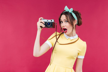 Amazed beautiful pinup girl in yellow dress holding old camera