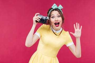 Cheerful pinup girl using vintage camera and taking pictures