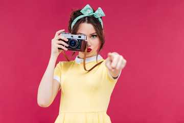 Serious cute woman using old camera and pointing on you