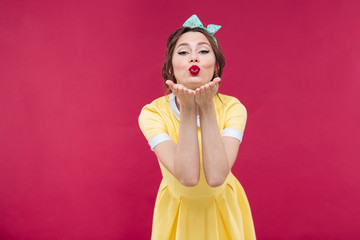 Happy pretty pinup girl in yellow dress sending a kiss