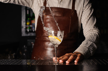 splash in a glass with lemon barman on background