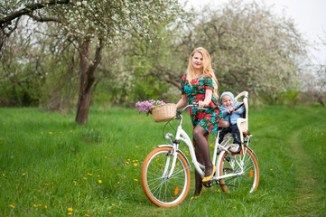 Mother with long blonde hair in dress keeps bicycle and baby in bicycle chair, in the basket lay a bouquet of lilacs, against of blooming fresh greenery in spring garden on the background