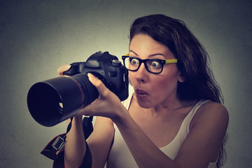 excited shocked woman with professional DSLR camera