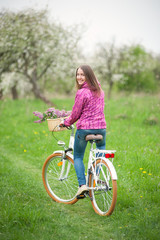 Brunette female girl wearing purple jacket and jeans and riding a vintage white bicycle with lilac flowers basket in spring garden. Rear view