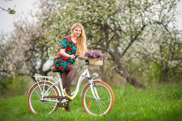 Young female biker with long blond hair wearing flowered dress and yellow shoes riding a vintage white bicycle with flowers basket, against the background of blooming trees in spring garden