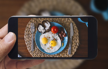 Taking picture of fried eggs and tomato with mobile phone. Phone in male hands.On the plate there is 2 fried eggs, tomato, bread with cheese. fork and knife. Vintage style.