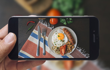 Taking picture of fried eggs and tomato with mobile phone. Phone in male hands.On the plate there is fried egg, tomato, sausage, parsley, beans, fork and knife. Vintage style. Top view.