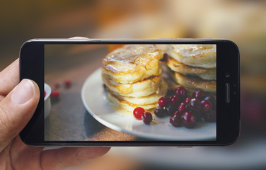 Taking picture of pancakes with mobile phone. Phone in male hands.On the plate there is pancakes with berries and honey.