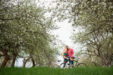 Loving young couple with bikes enjoying romantic holidays against the background of blooming trees and fresh greenery in spring garden