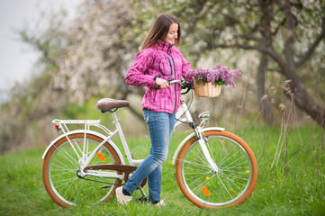 Beautiful brunette girl wearing purple jacket and jeans with a vintage white bicycle and lilac flowers basket, against the background of blooming trees, fresh greenery in spring garden