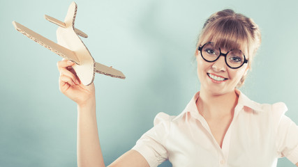 woman thinking about vacation holds airplane