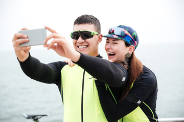 Cheerful couple cyclists making selfie photo