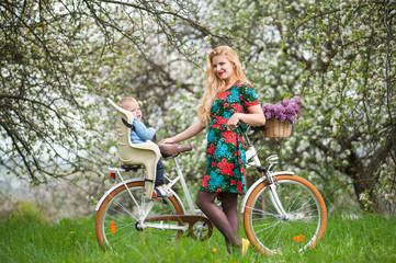 Smiling blonde female with long hair and red lips in flowered dress holding bike and baby in bicycle chair, in the basket lay a bouquet of lilacs. Blooming trees in spring garden on the background