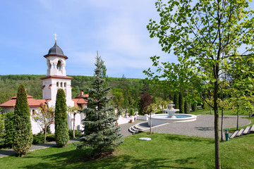 Bell tower and basin at orthodox Curchi monastery in Moldova with green trees and blue sky