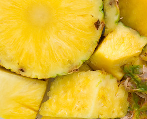 A fresh pineapple on a cutting board close view