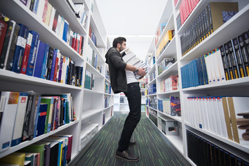 Student holding lot of books in school library
