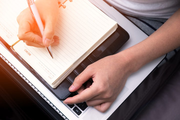 female hands with pen writing on notebook with laptop.