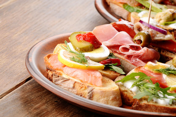 Open sandwiches with salmon, eggs, mussels, jamon and herring