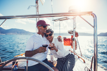 Mature couple toasting with red wine on yacht